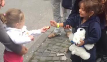 Conmovedora imagen de una niña alemana dando comida a refugiada siria