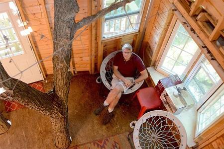 Un abuelo construye una casa de tres pisos en un árbol para sus nietos
