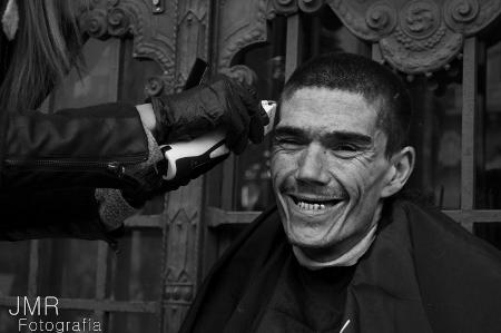 Jóvenes peluqueros cortan el pelo gratis a personas sin techo en Madrid
